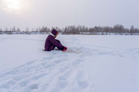 Lonely girl angler fishing with a winter fishing rod sitting on a substrate on the ice among the white snow.