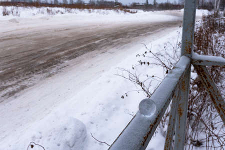 A small glass ball lies in the winter on the railing in the snow against the background of a turn in the muddy road.