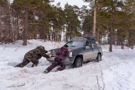Russia, Novosibirsk-March 23, 2020. Two unknown men push an off-road SUV