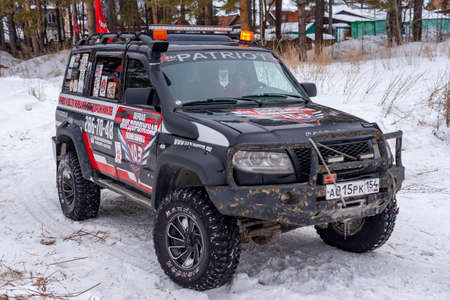 Russia, Novosibirsk-March 5, 2020. Prepared for off- road evacuation, the Russian 4x4 UAZ Patriot SUV with a protective bumper stands in the snow in winter. 新聞圖片