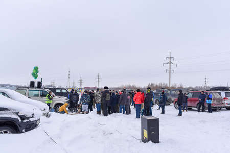 Russia, Novosibirsk-March 23, 2020. A lot of people on the Parking lot stand listening to a person speak into a microphone in winter.