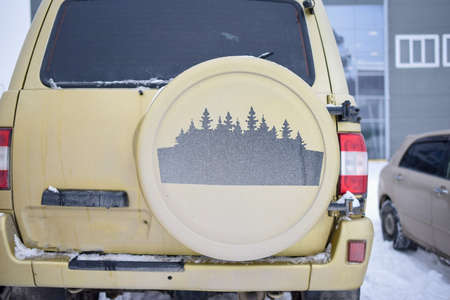 Russia, Novosibirsk-March 5, 2020. Drawing of forest trees on the spare wheel cover for a Russian 4x4 SUV