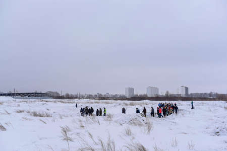 Russia, Novosibirsk-March 23, 2020. A lot of people take turns walking in the snow on an off-road highway in winter with cameras and selfie sticks.