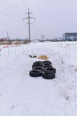 Russia, Novosibirsk-March 23, 2020. Old tires lie on the obstacle course in the background of a car dealership before the holidays for customers. 新聞圖片