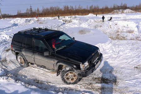 Russia, Novosibirsk-March 23, 2020. The 4x4 Jeep Grand Cherokee off-road vehicle with off- road training drives through snow in winter before making a sharp turn in a field. 新聞圖片
