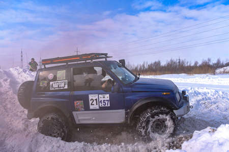 """Russia, Novosibirsk-March 13, 2020. Offroad SUV """"Suzuki Escudo"""" 4x4 quickly goes on a snowy road in the brown smoke, raising the wheels of a Blizzard."""