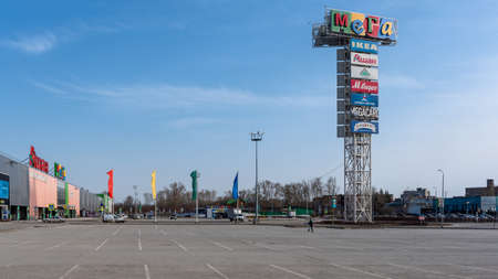 Novosibirsk, Russia-April 12, 2020. Empty Parking without cars and people at the Mega IKEA hypermarket due to the quarantine of the covid19 virus epidemic with a lone woman in a mask and grocery bags in her hands.