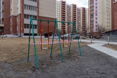 Novosibirsk, Russia-April 12, 2020. Swings on the Playground in the courtyard of an apartment building are taped closed to the public due to the quarantine of the covid 19 coronavirus epidemic. 新聞圖片