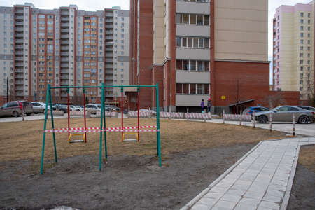 Novosibirsk, Russia-April 12, 2020. Children from afar look at the swings on the Playground in the courtyard of an apartment building covered with striped tape closed to the public due to the quarantine of the covid 19 coronavirus epidemic.