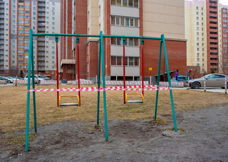 Novosibirsk, Russia-April 12, 2020. Children run on the street past swings on the Playground in the courtyard of an apartment building covered with striped tape closed to the public due to the quarantine of the covid 19 coronavirus epidemic. 新聞圖片