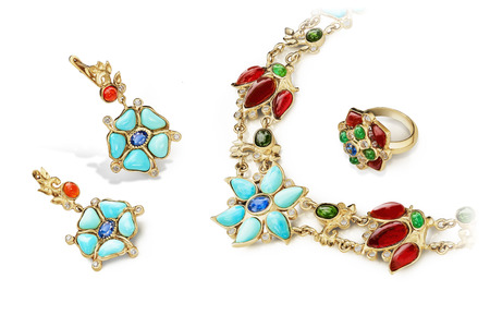 Elegant and fashion jewellery golden set of rings, earrings and necklace with rubies, sapphires, emeralds, turquoise and diamonds. Stock Photo