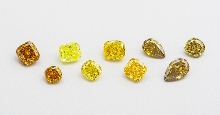 Set of luxury yellow and brown transparent sparkling gemstones of various cut shape diamonds collage on white background. Stock Photo