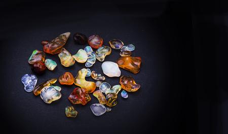 Set of transparent sparkling opals collage on black background.
