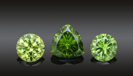Set of luxury green transparent sparkling gemstones of various cut shape demantoids collage isolated on black background.
