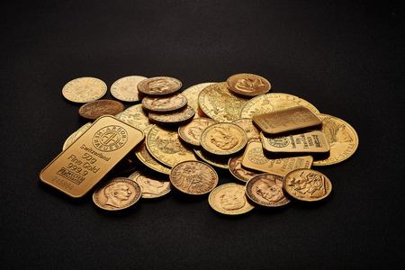 Yellow gold bars and coins isolated on black background.