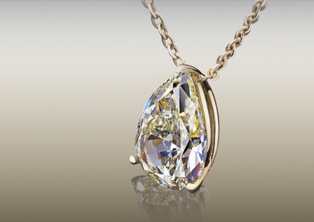 Beautiful yellow shape pear cut diamond pendant isolated on abstract background.