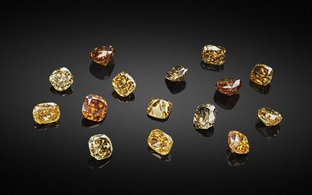 Set of luxury yellow and brown transparent sparkling gemstones of various cut shape diamonds collage on black background.