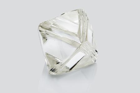 Diamant brut transparent isolé sur fond blanc.