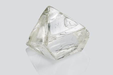 Transparante ruwe diamant geïsoleerd op een witte achtergrond. Stockfoto