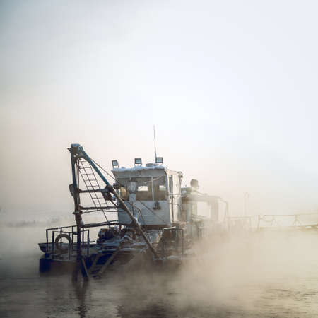clarifier: dredge boat in the fog in winter Stock Photo