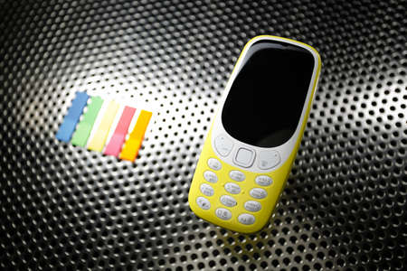 Yellow phone on metal surface Stock Photo