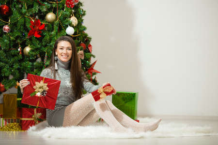 Portrait of happy young woman christmas present boxes in front of christmas tree