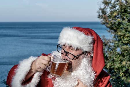 Fat man dressed as Santa drinking beer on the ocean