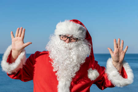 Santa's vacation at sea. Relaxing on the beach Stock Photo
