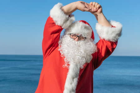 Santa doing exercises on the ocean Stock Photo