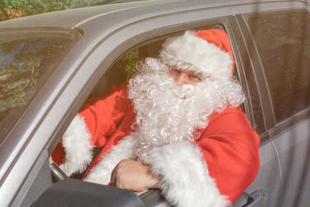 A man dressed as Santa Claus delivers gifts on the car
