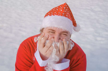 Funny fat man dressed as santa claus is sitting on the snow Stock Photo