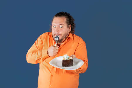 Funny fat man in orange shirt with a piece of chocolate cake on a plate. Birthday celebration