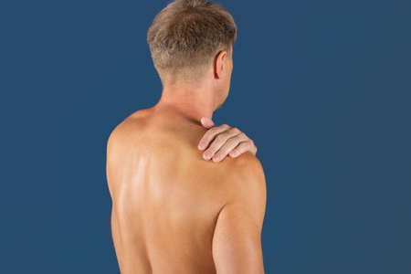 Man holding his sore shoulder trying to relieve pain Stock fotó