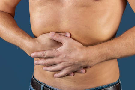 Man holding his stomach in pain. Man with naked torso experience stomachaches on blue background