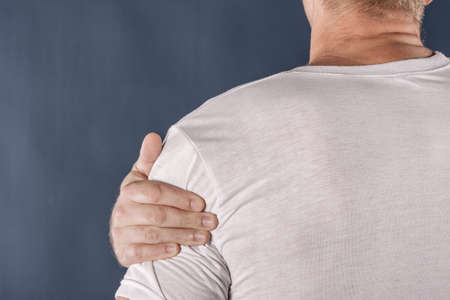 Man holding his sore shoulder trying to relieve pain Stock Photo