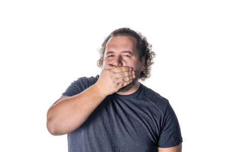 Portrait of amazed man covering his mouth over white background. Say no evil concept