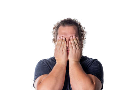 Portrait of a man covering his eyes with hands. See no evil concept. Emotions facial expressions and communication signs