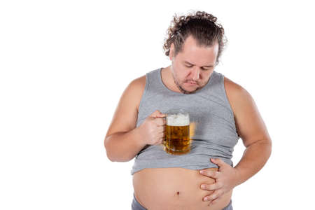 Funny fat man feeling happy and relaxed, holding fresh cold beer in his hands