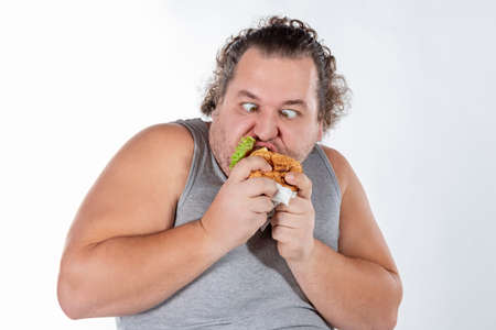 Portrait de drôle de gros homme mangeant un hamburger de restauration rapide isolé
