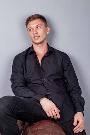 Handsome man wearing black shirt sitting on the leather sofa Stock Photo