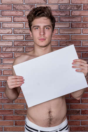 Young guy posing in underwear with a billboard
