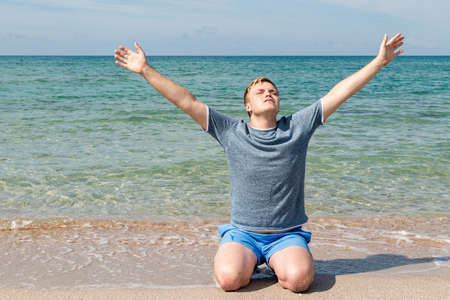Young man in a t-shirt on the seashore and looks at the sea