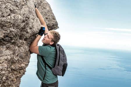 Young man climbing, hanging on edge