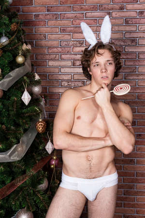 Handsome naked guy in suit rabbit celebrating christmas over brick wall