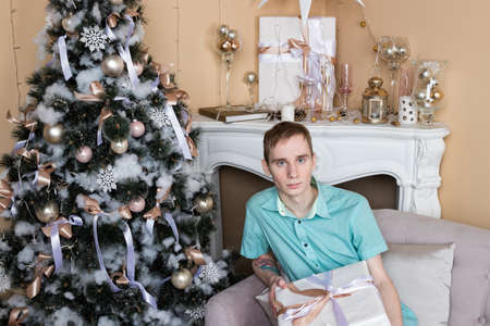 Young man christmas sitting on couch near christmas tree