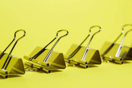 Metal binders on a yellow background. Stationery accessories. Paper clip