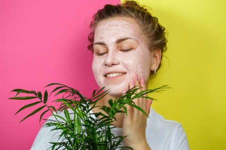 Beautiful young girl with a refreshing mask on her face. Holding a decorative palm in his hands. Beauty and healthy skin