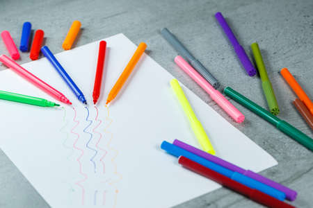 many multi-colored markers for drawing with drawings on white paper