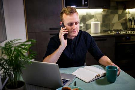ビジネスマンは、ラップトップで作業し、自宅で仕事をし、思慮深く、将来を心配し、電話で話し、株式市場の動向、メッセージ、ウイルス検疫時間