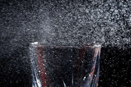 Black background on it is a close-up of a clean glass in a hand. Spray on a glass of water. Insulated glass